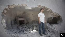 這名男子星期六在政府組織的下現場參觀中這名站在遭到空襲的卡扎菲的住處