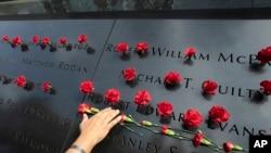 Norma Molina, de San Antonio, Texas, coloca flores en los nombres de bomberos en el Memorial del 11 de septiembre en la ciudad de Nueva York el 9 de septiembre, de 2019.