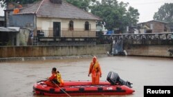 A rescue team set up a line across the swollen Ciliwung river in Jakarta, Indonesia, Feb. 5, 2018.