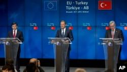 ນາຍົກລັດຖະມົນຕີ ເທີກີ ທ່ານ Ahmet Davutoglu (ຊ້າຍ), ປະທານສະພາບັນດາປະເທດຢູໂຣບ ທ່ານ Donald Tusk (ກາງ) ແລະ ປະທານຄະນະກຳມາທິການ ບັນດາປະເທດຢູໂຣບ ທ່ານ Jean-Claude Juncker ກ່າວຖະແຫລງຕໍ່ສື່ມວນຊົນ ໃນກອງປະຊຸມຖະແຫລງຂ່າວ ຢູ່ທີ່ກອງປະຊຸມສຸດຍອດ ລະຫວ່າງ EU-Turkey ໃນນະຄອນບຣັສໂຊລສ໌ ເມື່ອວັນອາທິດຜ່ານມາ, ວັນທີ 29, 2015.
