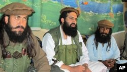 FILE - Pakistani Taliban spokesman Shahidullah Shahid (C), flanked by bodyguards, is seen talking to reporters at an undisclosed location in Pakistani tribal area of Waziristan, Oct. 5, 2013.