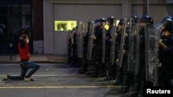Čovek na kolenima ispred kordona policije u Sent Luisu, u Misuriju (Foto: Reuters/Lawrence Bryant)