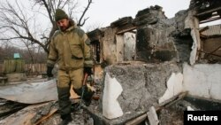 A member of a rebel unit of the self-proclaimed separatist Donetsk people's republic walks past a house destroyed by shelling in the village of Olenivka, south of Donetsk, Feb. 7, 2015.