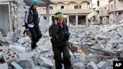 FILE - Kurdish female fighters move to another secured point in the contested zone of Kobani, Syria, on Nov. 19, 2014.