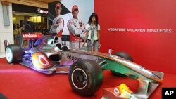 Promotions for the first ever Indian Formula One race are taking place across the country. A model stands next to a Formula One replica at a mall in Ahmedabad, Oct. 17, 2011.
