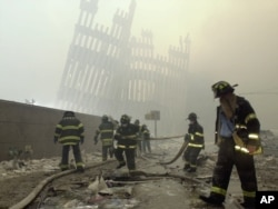 FILE - With the skeleton of the World Trade Center twin towers in the background, New York City firefighters work amid debris on Cortlandt Street after the terrorist attacks, Sept. 11, 2001.