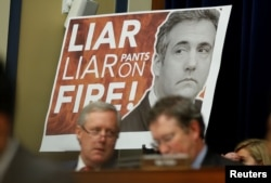 "A sign reading ""Liar Liar Pants on Fire!"" is seen behind Rep. Mark Meadows (R-NC) and other Republican members of the committee during the testimony of former Trump personal attorney Michael Cohen at a House Committee on Oversight and Reform hearing on Capitol Hill, Feb. 27, 2019."