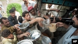 Pakistani men and boys gather to receive food at a camp for the displaced set up inside a college on the outskirts of Nowshera, 2 August 2010