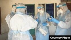មន្ត្រីសុខាភិបាលមួយក្រុមស្ថិតក្នុងសម្លៀកបំពាក់តាមក្បួនខ្នាត ខណៈពួកគេកំពុងបំពេញកិច្ចការគ្រប់គ្រង និងទប់ទល់ការឆ្លងរាលដាលនៃវីរុសកូរ៉ូណានៅកម្ពុជា។ (រូបថតដោយ៖ នាយកដ្ឋានប្រយុទ្ធនឹងជំងឺឆ្លង CDC)