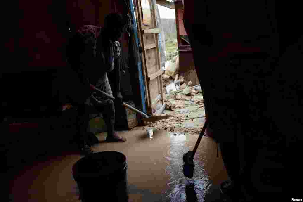 People try to clean the mud at their damaged house after Hurricane Matthew passed Jeremie, Haiti, Oct, 6, 2016.