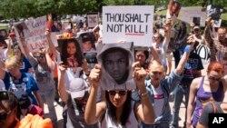 星期六在美国步枪协会年会会场外要求严格控制枪支的示威者为枪下丧生者举行默哀