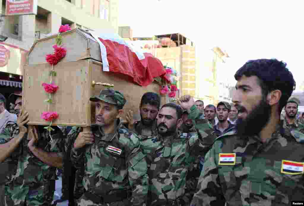 Mourners carry the coffin of a Shi'ite volunteer from the brigades of peace, who joined the Iraqi army and was killed during clashes with militants in Samarra, during his funeral in Najaf, Iraq, July 6, 2014.