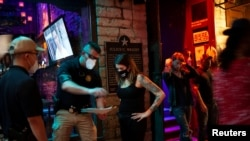 Lindsey Pettita (ketiga dari kiri), manajer bar The Jackalope berbincang dengan petugas pengawas minuman alkohol Texas untuk memeriksa aturan jarak aman untuk meredam penyebaran virus corona (Covid-19), setelah bar buka kembali, di Austin, Texas, 22 Mei 2