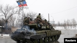 FILE - Troops from the separatist self-proclaimed Donetsk People's Republic drive an armored vehicle on the outskirts of Donetsk, Jan. 22, 2015.