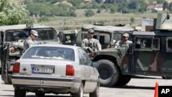 US soldiers serving in KFOR check vehicles from Serbia entering Kosovo after reopening a checkpoint in this July 2011 file photo. Serbia and Kosovo recently came to agreement on managing their joint border crossings.
