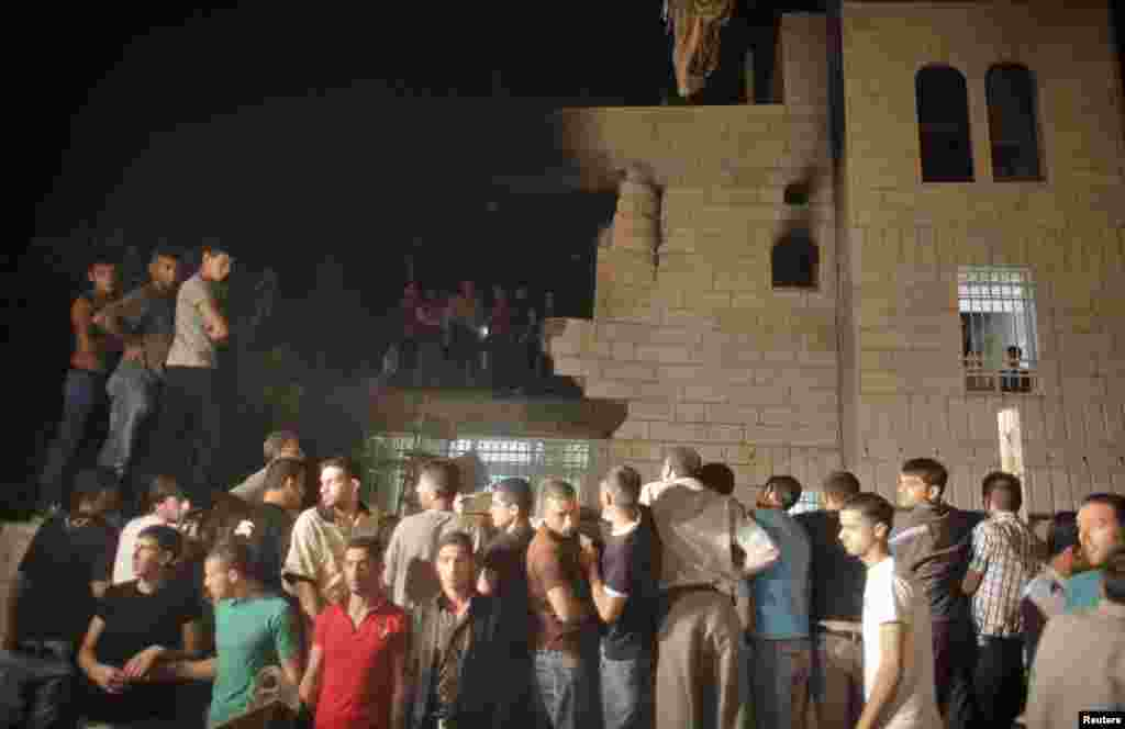 People gather following a blast at the family home in Hebron of one of the men Israel accuses of kidnapping three teenagers who were later found dead, July 1, 2014.