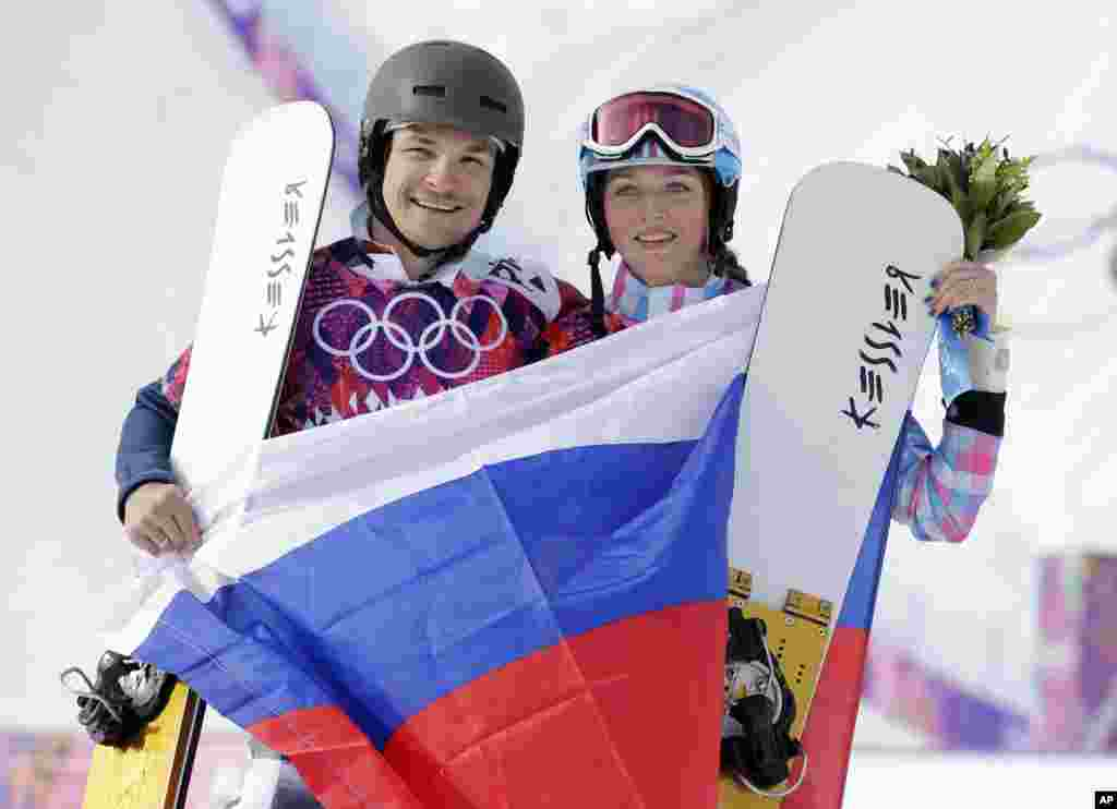 Russia's Vic Wild (left) poses after winning the gold medal in the men's snowboard parallel giant slalom final, with his wife and bronze medalist in the women's snowboard parallel giant slalom final, Russia's Alena Zavarzina, Krasnaya Polyana, Russia, Feb. 19, 2014.