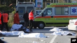 Sheets cover the bodies of cyclists after a speeding car, partially seen at right, plowed head-on into their group in southern Italy on Sunday morning, killing eight of them, in Lamezia Terme, Italy, 05 Dec 2010