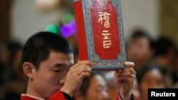 资料照:北京一家天主教堂在做圣诞弥撒时一名神职人员手举圣经。(2014年12月24日)