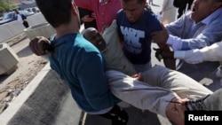 리비아 수도 트리폴리에서 15일 시위대와 경찰이 충돌한 가운데, 시위 참가자들이 부상자를 옮기고 있다.