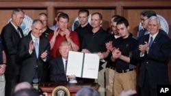 President Donald Trump, accompanied by coal miners and Interior Secretary Ryan Zinke.