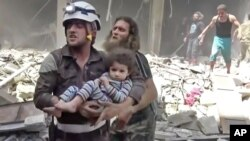 In this image made from video and posted online from Validated UGC, a Civil Defense worker carries a child after airstrikes hit Aleppo, Syria, April 28, 2016.