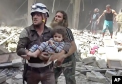 FILE - In this image made from video and posted online from Validated UGC, a Civil Defense worker carries a child after airstrikes hit Aleppo, Syria, April 28, 2016.