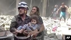 Ảnh chụp từ video được đăng tải trên mạng Validated UGC cho thấy nhân viên cứu hộ đang mang một đứa trẻ ra khỏi khu vực bị tấn công ở Aleppo, Syria, ngày 28/4/2016.
