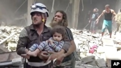 Petugas Pertahanan Sipil menggendong anak kecil menyusul serangan-serangan udara yang menghantam Aleppo, Suriah (28/4).