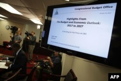 FILE - Members of the press cover a Congressional Budget Office (CBO) media briefing in Washington, D.C., Jan. 24, 2017.