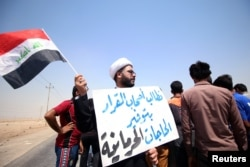 "FILE - A protester holds a sign that reads ""We ask the decision makers to provide the things we are deprived of"" during a protest in south of Basra, Iraq, July 16, 2018."