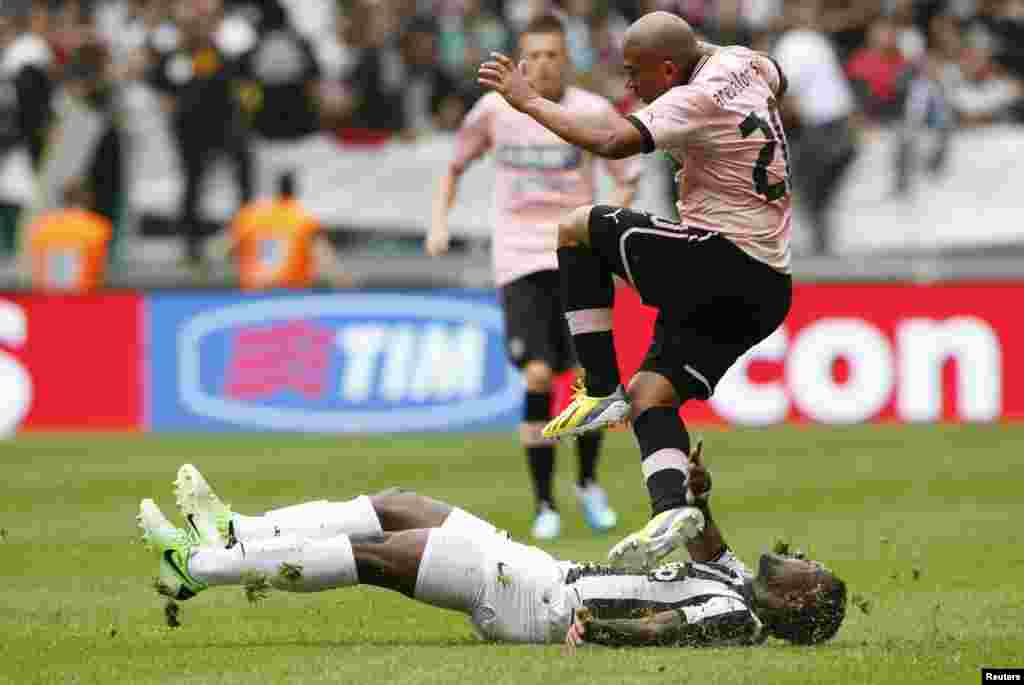 Juventus' Kwadwo Asamoah is tackled by Palermo's Egidio Arevalo Rios (top) during the Italian Serie A soccer match at the Juventus stadium in Turin, Italy.