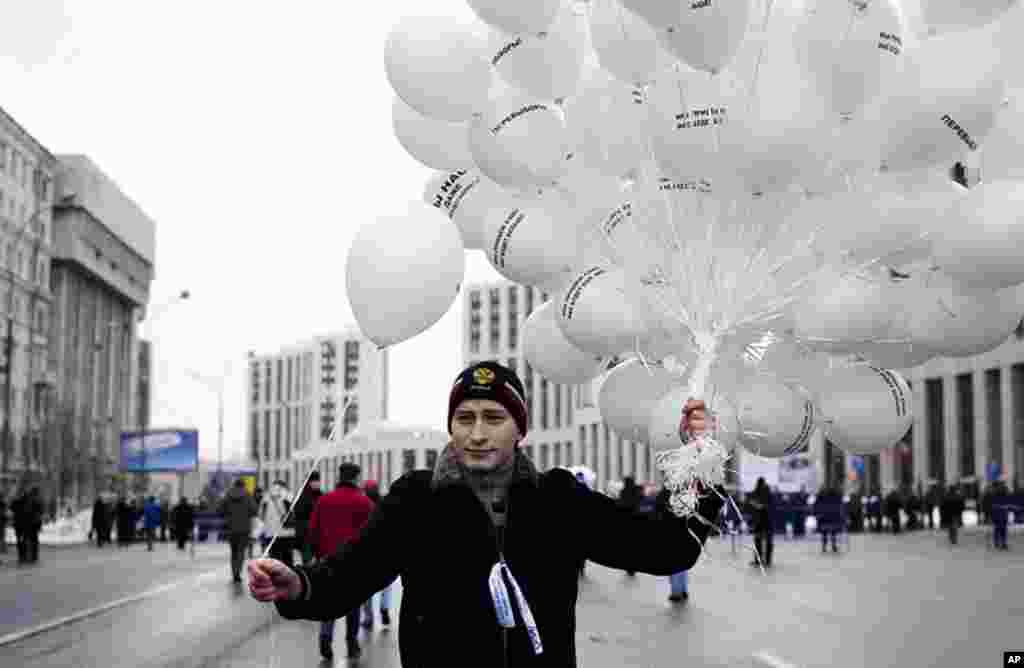 A protester hands out white balloons at the rally. The white balloons were a symbol of peaceful protests, December 24, 2011. (VOA - Y. Weeks)