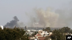 Smoke rises above buildings following a NATO air strike in Tripoli, Libya, April 14, 2011.