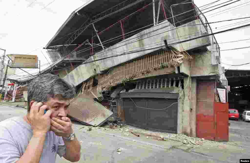 Seorang warga berjalan melewati sebuah gedung yang runtuh setelah gempa 7,2 Richter melanda kota Cebu di Filipina tengah.