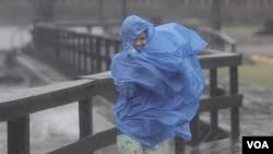 Alora Goldsmith harus berjalan melawan angin dan hujan selagi badai Irene menghantam Elizabeth City, North Carolina (Sabtu, 27/8).