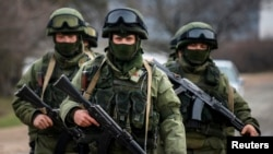 Armed men, believed to be Russian servicemen, march outside an Ukrainian military base in the village of Perevalnoye near the Crimean city of Simferopol March 9, 2014. Shots were fired in Crimea to warn off an unarmed international team of monitors and at