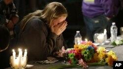 Seorang gadis remaja menutup wajahnya saat berlutut di tempat doa bersama di gereja bagi korban penembakan di SMA Marysville Pilchuck (24/10). (AP/Ted S. Warren)
