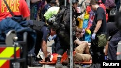 """Rescue workers assist people who were injured when a car drove through a group of counter protestors at the """"Unite the Right"""" rally Charlottesville, Virginia, Aug. 12, 2017."""