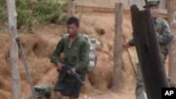 In this undated photo released by Free Burma Ranger, Myanmar soldiers walk through a village in Karen state, Myanmar. Myanmar's army has moved reinforcements into ethnic minority areas for the probable renewal of an offensive whose past human rights viola