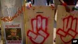 Manifestantes anti-golpe com escudos improvisados fazendo a saudação com três dedos junto à imagem imagem desfigurada do comandante-chefe, general Min Aung Hlaing, em Yangon, Myanmar, 9 Março 2021