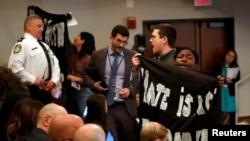 Активисты прерывают выступление Кевина Макалинана на конференции по иммиграционной политике