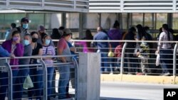Travelers, left, waiting in line to cross a customs area into the United States at the McAllen-Hidalgo International Bridge look on as a group of migrants, right, are deported to Reynosa, Mexico, March 18, 2021, in Hidalgo, Texas.