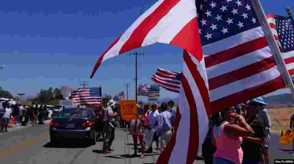 旗帜鲜明的示威民众等待大巴(美国之音国符拍摄)