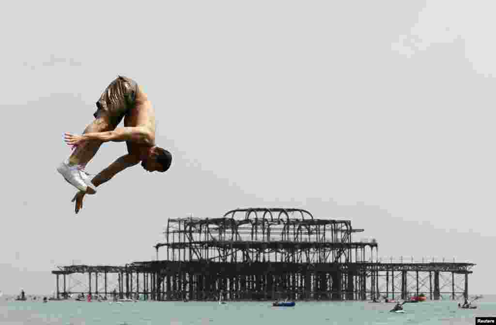 A man dives into the sea by Brighton's West Pier during the hot, sunny weather in Brighton Southern England.
