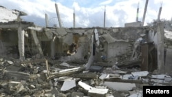 Buildings damaged by what activists said were missiles fired by a Syrian Air Force fighter jet operated by forces loyal to Syrian President Bashar al-Assad are seen at Houla, near Homs December 6, 2012.