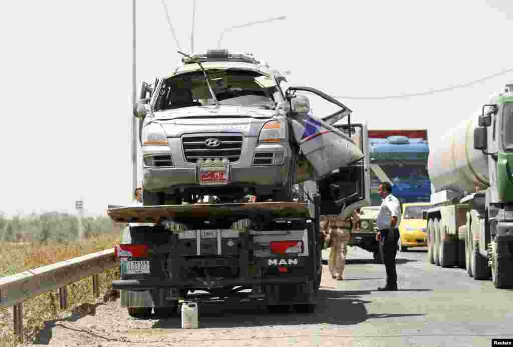 Police prepare to remove a damaged vehicle from the site of a bomb attack in Taji, Iraq, June 17, 2013.