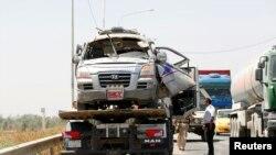 Một chiếc xe bị hư hỏng sau vụ đánh bom được đưa ra khỏi hiện trường ở Taji, ngày 17/6/2013.
