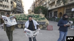 Anti-government demonstrators read newspapers just in front of an armored vehicle in Tahir, Cairo's main square, Egypt, February 2, 2011