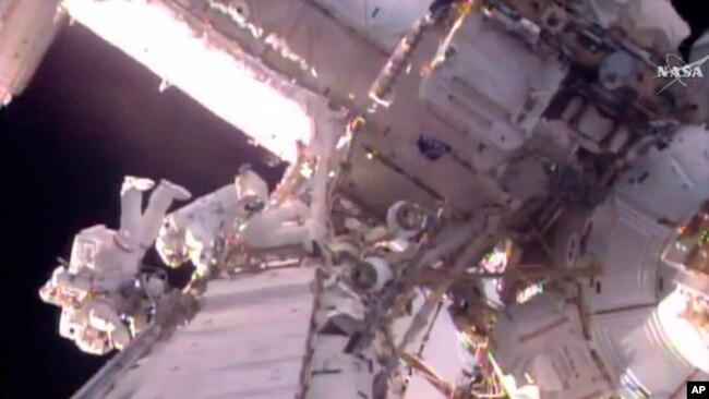 Esta imagen tomada de un video proporcionado por la NASA muestra al astronauta estadounidense Shane Kimbrough, a la izquierda y al astronauta francés Thomas Pesquet durante un paseo espacial fuera de la Estación Espacial Internacional, el 13 de enero de 2017.